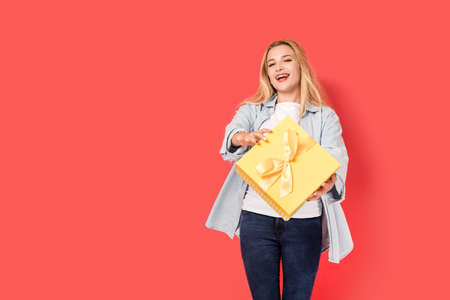 Blonde girl is surprised by gift. Picture includes copy space