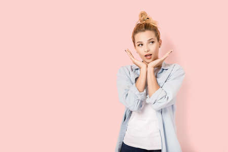 Pretty blonde woman on pink background with copyspace