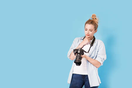 Young blonde photographer holds looks at the photo she made and thinks