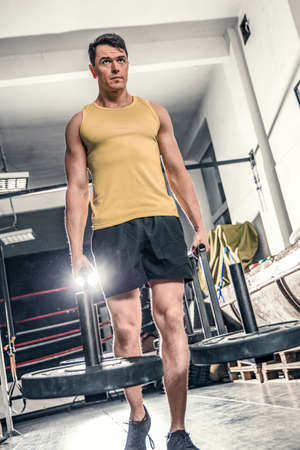 Man performs an exercise called farmers walk in the gym. Photos taken on an atmospheric old gym