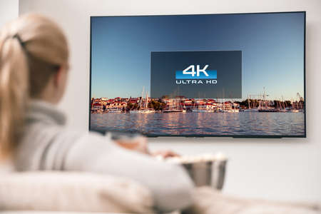 Big modern TV with 4k resolutions and young woman on foreground watching some video Stock Photo
