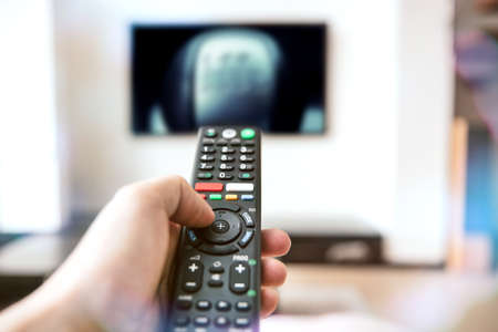 Human hand holds a remote control for a modern television