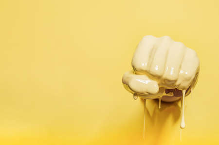 Fist painted with yellow paint pierces the wall