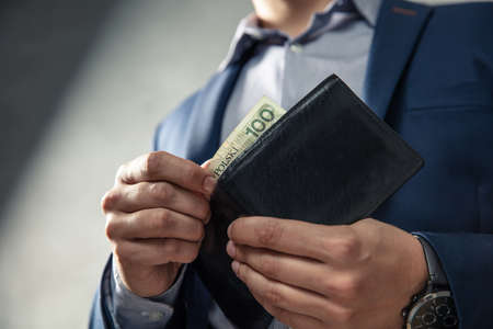 Elegant man in suit pulls out his money from wallet. Conception of money management.