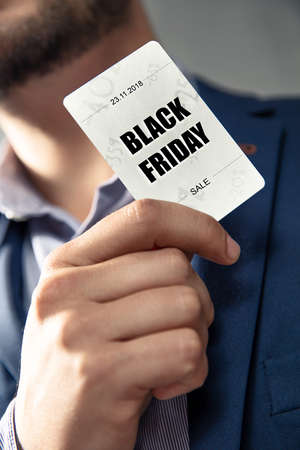 Black Fridays Sale card holded by an elegant man in suit. Conception of Black Fridays sales and discounts at shops.