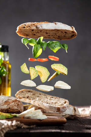 Isolated ingredients for a sandwich floating in air in layers with a crispy ciabatta bread, fresh basil, tomatoes, mozzarella and avocado over rustic table with olive oil in the background. Banco de Imagens
