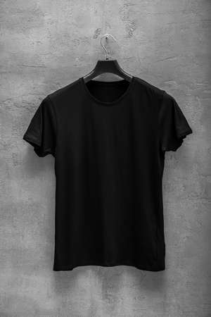 Front side of male black cotton t-shirt on a concrete wall. T-shirt without print