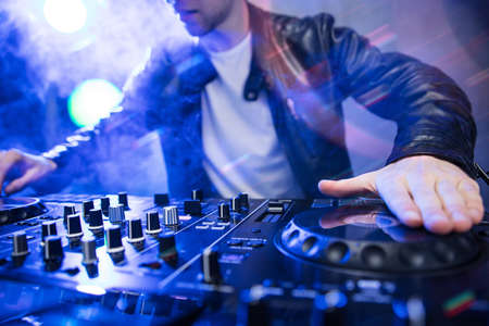 Dj mixing at party festival with red light and smoke in background - Summer nightlife view of disco club inside. Focus on hand Standard-Bild
