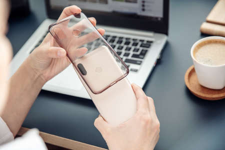Womans hands put silicone case on the back side of smartphone. 写真素材