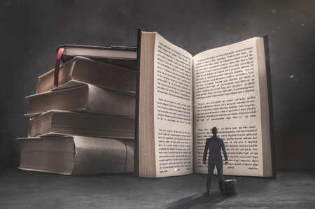 Surrealistic image of businessman looking at big open book in dark room. 写真素材
