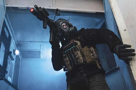 Un soldat de l'unité spéciale avec un masque à gaz sort de l'ascenseur industriel et vise une cible
