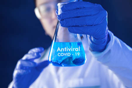 Lab worker holds flask with antiviral medicines. Conception of studies about corona