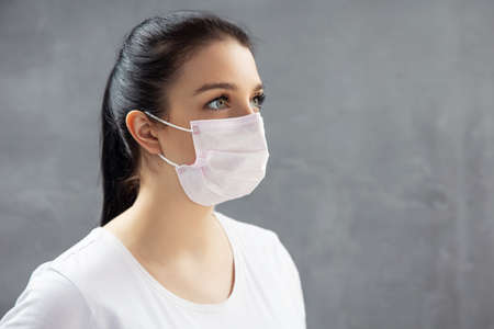Young woman in medical mask on concrete background. Stock Photo