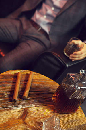 Two cigars and a carafe of whisky on wooden table and an elegant man with the glass of whisky in the background. Vertical view. Stock Photo