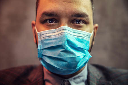 Young elegant man with medical mask on his face.