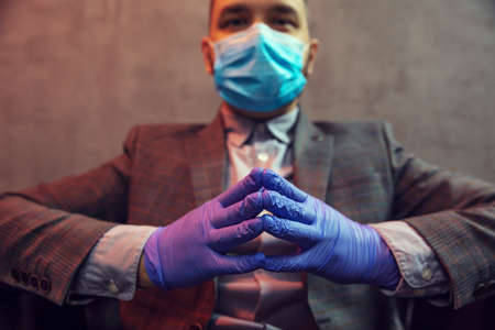 Young elegant man sits in a leather armchair with mask on his face and medical gloves on concrete background. Close up on hands. Stock Photo