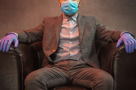 Young elegant man sits in a leather armchair with mask on his face and medical gloves on concrete background.