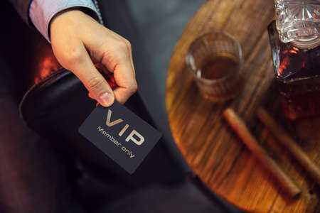 Man holds VIP member card. View from the top on the gentleman's hand that holds exclusive VIP membership card next to the wooden table with whisky in carafe and glass with cigars. Stock Photo