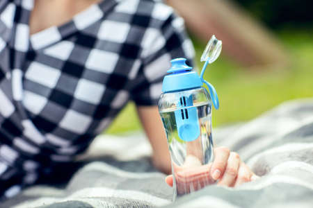 Woman holds the bottle of filtered water outdoors. Woman relaxes outdoors and holds the reusable bottle of fresh filtered water in hand. Stock Photo