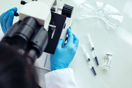 Female scientist uses microscope. Female scientist in protective gloves uses medical microscope with syringes, protective glasses and phial next to it
