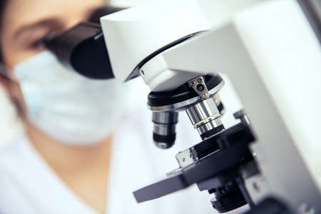Microscope is used by woman. Medical microscope and female scientist in protective mask in the background