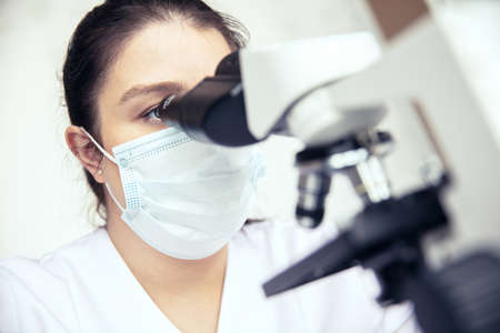 Woman uses a microscope. Female scientist examines sample with medical microscope Stock Photo