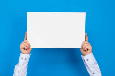 Hands hold white board on blue background with copy space for your text.