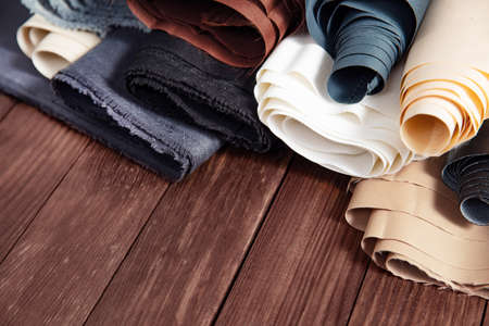 Beles of fabric on wooden background.