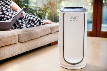 Air purifier cleans up air. Modern air purifier cleans up the air in the living room with woman lying on the couch. logo on the device was created in graphic program Stock Photo