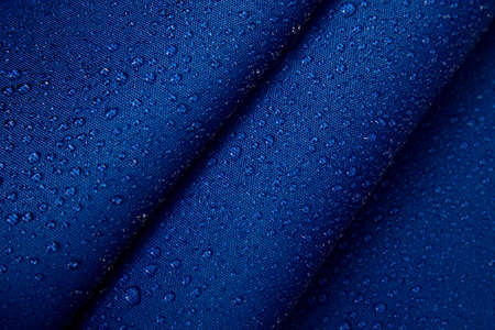 Abstract background of hydrophobic fabric. Drops of water on creased blue fabric.
