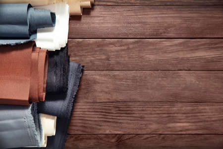 Beles of fabric on wooden background. View from the top.