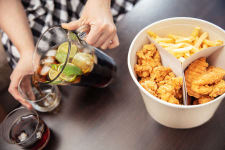 Dinner made of fast food. French fries and fried chicken in box and young woman pours cola to the glasses. Stock Photo
