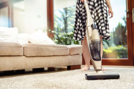 Hoovering the living room. Young woman hoovers up carpet in living room using handheld vacuum cleaner Stock Photo