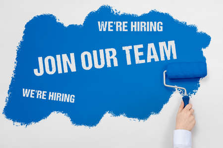 Hand holds a paint roller and paints white wall with blue paint and Join our team and We're hiring signs