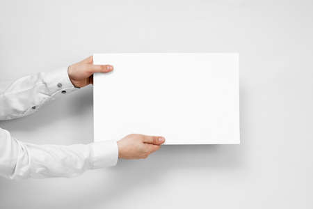 Hands hold from the left white board with copy space on white background.