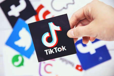 WROCLAW, POLAND - August, 29th 2020: Hand holds TikTok logo over another social media symbols. TikTok is a Chinese video-sharing social networking service Editorial