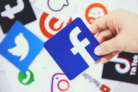 WROCLAW, POLAND - August, 29th 2020: Hand holds Facebook logo over another social media symbols. Facebook is an American online social media service based in Menlo Park, California Editorial