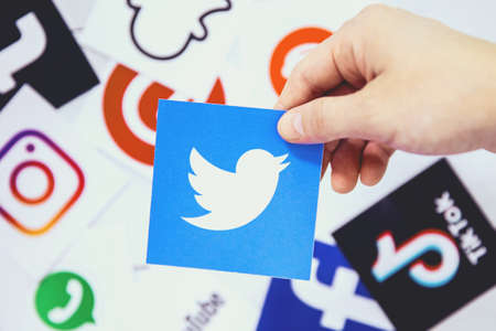 WROCLAW, POLAND - August, 29th 2020: Hand holds Twitter logo over another social media symbols. Twitter is an American microblogging and social networking service on which users post and interact with messages known as