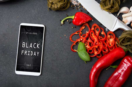 Modern smartphone with black friday banner on the screen lies on countertop with spicy vegetables