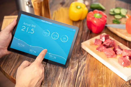 Tablet with application for BMI calculate over kitchen table with healthy food. Application on the screen created in graphic program. Stock Photo