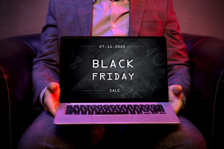 Black friday banner on the display of a modern laptop that is holds by an elegant man.