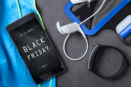 Smartphone with black friday banner lying on the stone slab with sport accessory