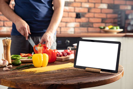 Tablet on the kitchen table and man preparing delicious and healthy food on background. Tablet screen with empty space.
