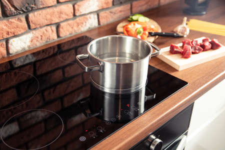 Metal pot stands on a modern induction cooker