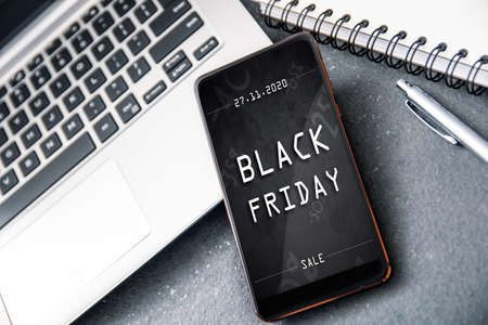 Smartphone with black friday banner on the screen lying on desk. Conception incoming promotion in e-commerce Stock Photo