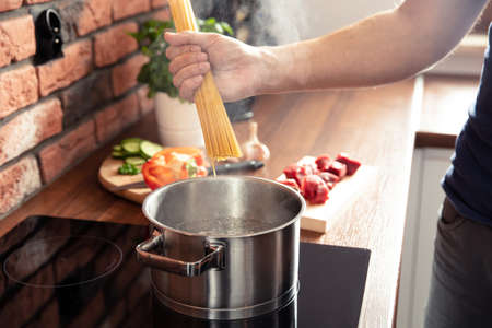 Man's hand throws spaghetti noodles into boiling water Stock Photo