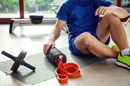 Various types of exercise equipment on the floor next to the young man Stock Photo