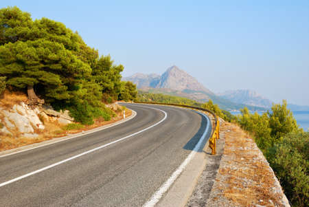 Winding Tarmac Road above blue sea photo