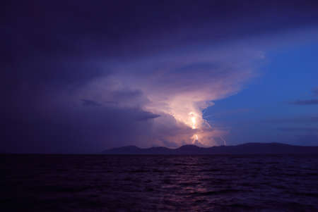 Storm and Lightning over and island and sea photo