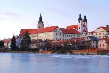 unesco in czech republic: Telc historic chateau and church towers in sunset light